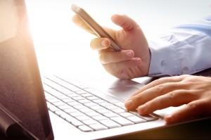 computer-laptop-mans-hands-holding-phone-shutterstock_112692412-e1408386036153